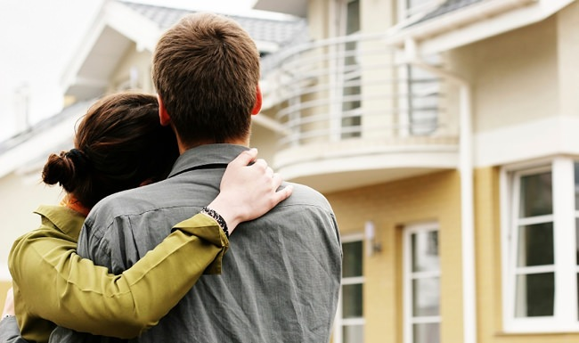 young couple looking up at an apartment balcony from the street